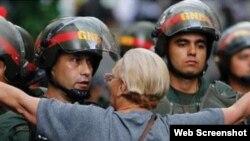 Una mujer venezolana trata de impedir el avance de agentes de la Guardia Nacional Bolivariana.