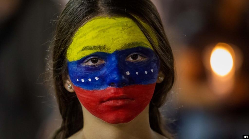Una mujer con el rostro pintado con los colores de la bandera venezolana participa en una protesta en Caracas.