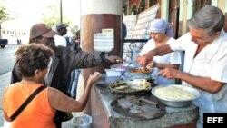 Una pareja de vendedores de frituras atiende a sus clientes en La Habana (Cuba).