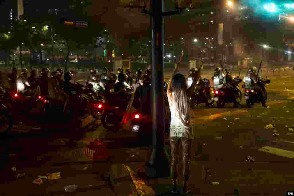 Una mujer hace un llamado a la paz mientras protestantes se enfrentan con miembros de la Guardia Nacional Bolivariana (GNB)