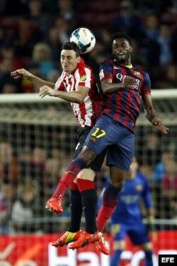 El camerunés, Alexandre Song, salta por el balón con Aritz Aduriz, del Atlético