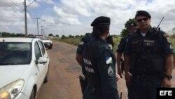Policías hacen una barricada para impedir el paso a periodistas y familiares de reos a la prisión de Boa Vista, donde ocurrió la masacre.
