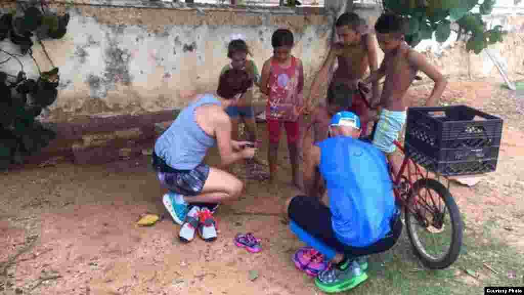 García y su esposa conversan con algunos de los niños a quienes han regalado tenis. Foto tomada del Facebook de Run Across Cuba.