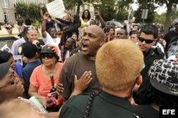 La policía pide a Shawn Caldwell (C) que se calme, mientras discute con un partidario de George Zimmerman.