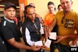 Tres cubanos muestran un documento que certifica que fueron atendidos en un centro de salud del país en diciembre.