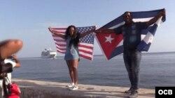 Dos cubanos, con las banderas de Cuba y Estados Unidos, esperan la llegada del Adonia en el Malecón habanero.
