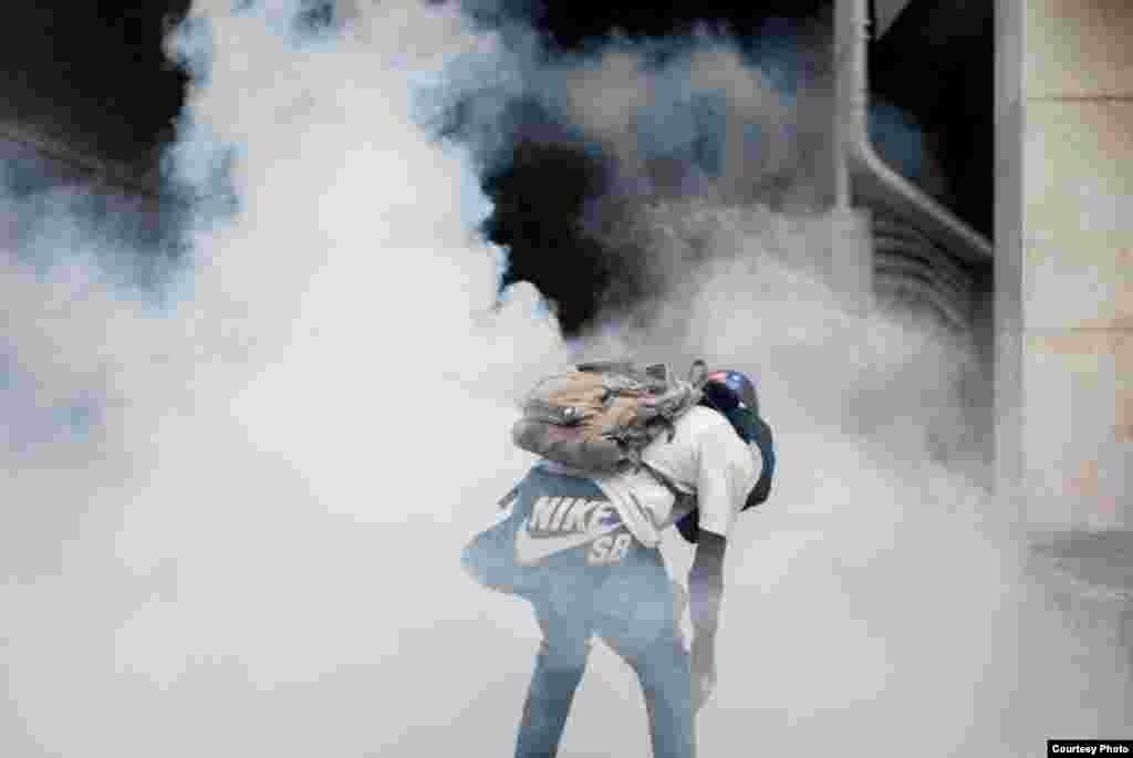 Manifestante resiste en medio de una nube de gas lacrimógeno. (Foto: Juan Pablo Arraez)