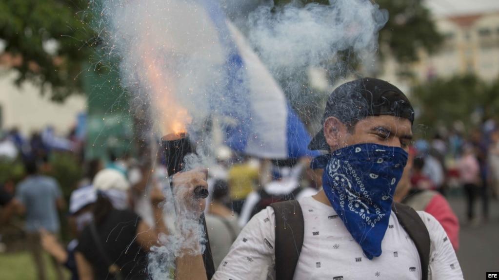 Un joven lanza mortero durante una multitudinaria marcha en apoyo a los estudiantes nicaragüenses.