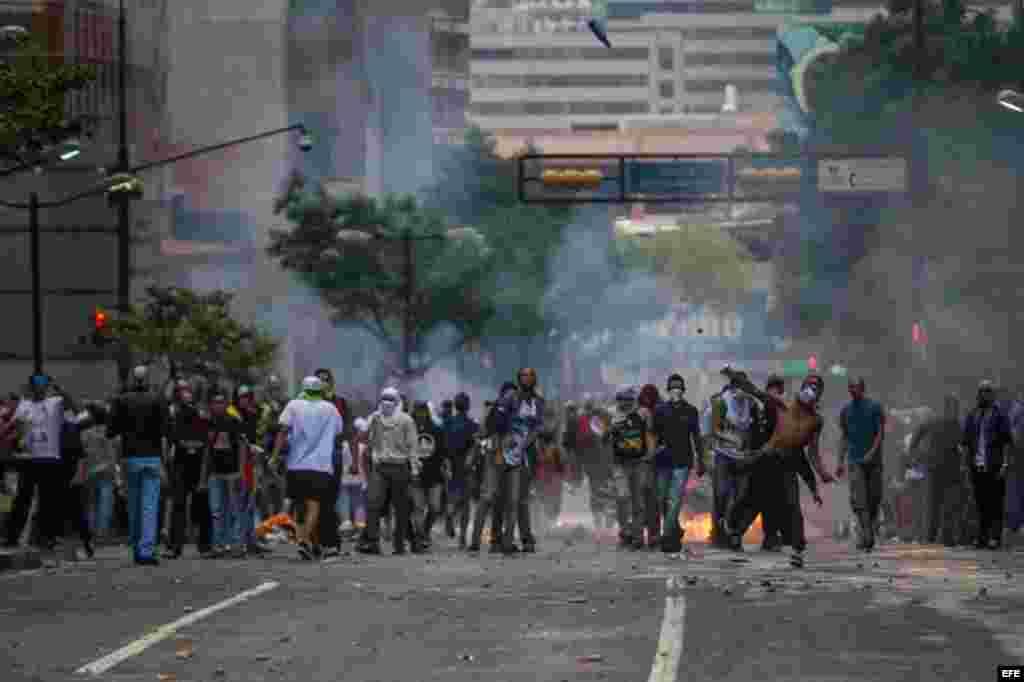 Manifestantes se enfrentan a miembros de la Guardia Nacional Bolivariana (GNB) hoy, jueves 12 de febrero de 2015, durante protestas en recuerdo de los fallecidos hace un año al término de una manifestación de la oposición, lo que dio inicio a un ola de pr