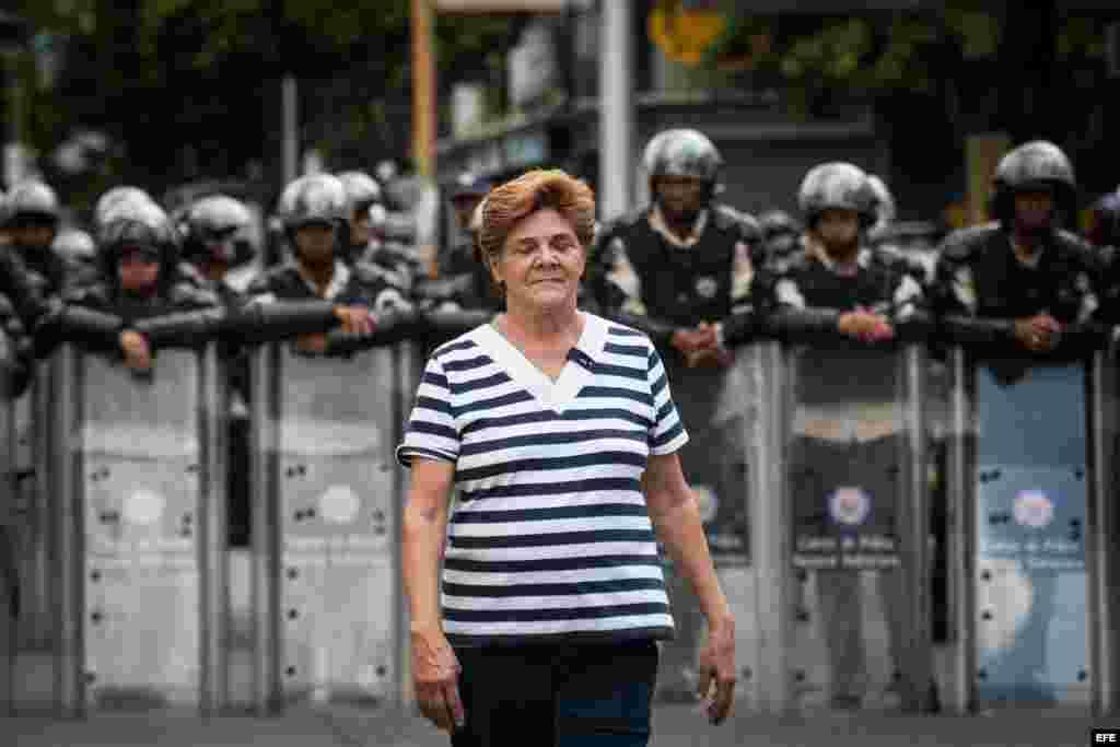 Una mujer camina cerca a policías antimotines mientras estudiantes opositores al Gobierno y profesores universitarios protestan en Caracas (Venezuela).