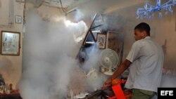 Un hombre fumiga una vivienda en La Habana Vieja, Cuba.