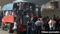 Varias personas intentan subir a un camión particular que funciona como transporte público