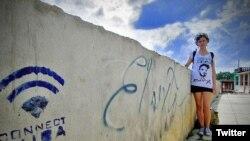 La bloguera disidente cubana Lia Villares junto a un grafiti con el nombre de El Sexto en una calle de La Habana.