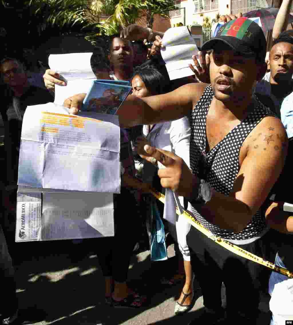 Un hombre, con un pasaporte en su mano y algunos documentos que confirman sus planes de viaje, protesta frente a la embajada de Ecuador en La Habana.