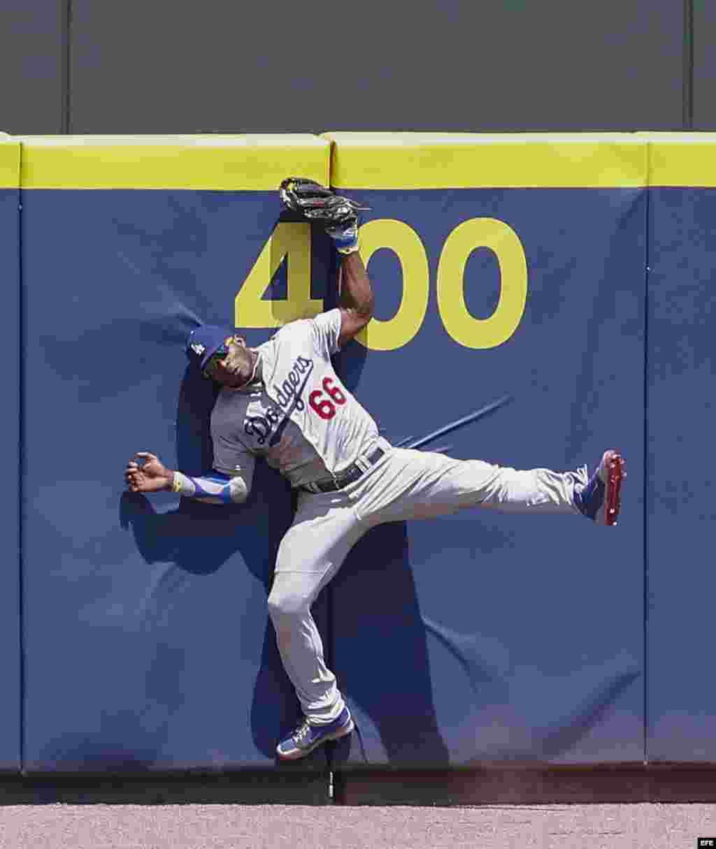 Yasiel Puig, captura una pelota en el aire, lanzada contra el muro por el primer base de los Bravos de Atlanta, Freddie Freeman.