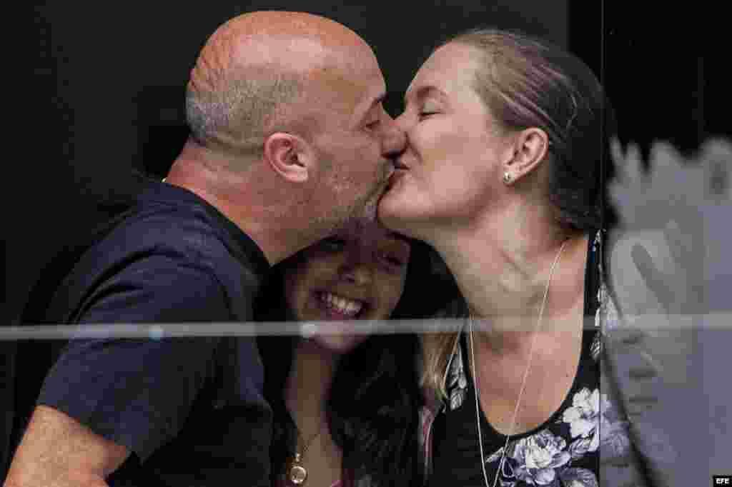 Ivan Simonovis (i) besa a su esposa Bonny (d) junto a su hija, Ivana (c).