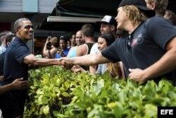 Obama (izda), saluda a varias personas durante un paseo en Kailua, Hawai.