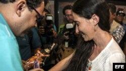 """La disidente cubana Yoani Sánchez (d), autora del blog """"Generación Y"""", recibe del cineasta Dado Galvao (i), su anfitrión en Brasil, una cinta de """"Senhor do Bonfim"""" hoy, lunes 18 de febrero de 2013, en el aeropuerto internacional Guararapes, de la ciudad d"""