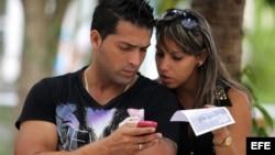 Dos jóvenes usan un teléfono móvil en La Habana.