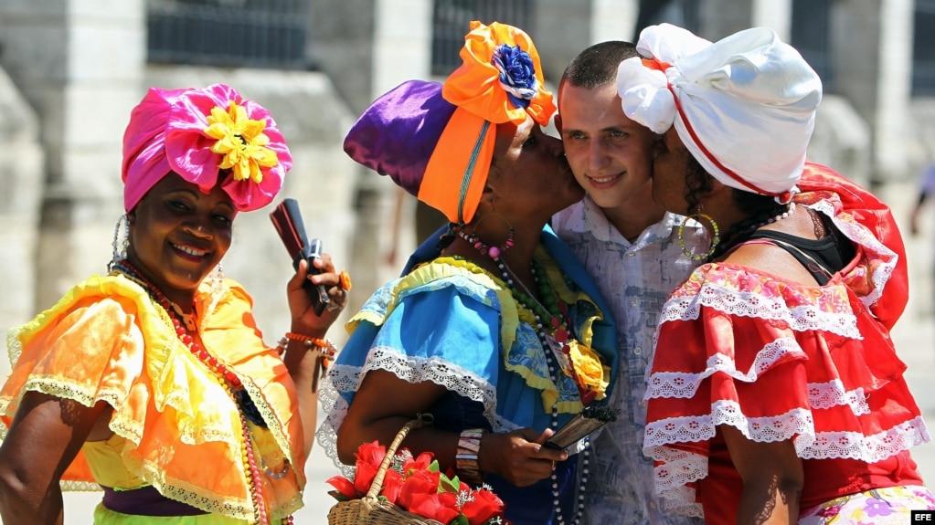 Un turista ruso se toma fotos con mujeres cubanas en la Plaza de Armas de La Habana. (Archivo)