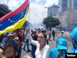 La opositora María Corina Machado sostiene una bandera venezolana al revés en protesta contra el gobierno de Maduro.