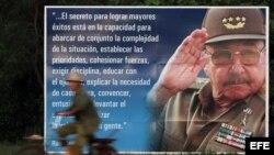 Un campesino pasea en bicicleta junto a un cartel con la imagen de Raúl Castro.
