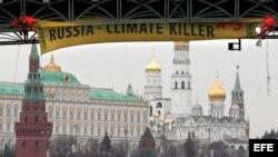 ARCHIVO. Activistas de Greenpeace colocan un afiche gigante con el mensaje 'Rusia - Asesino del Clima' en un puente sobre el río Moskva, frente al Kremlin de Moscú.