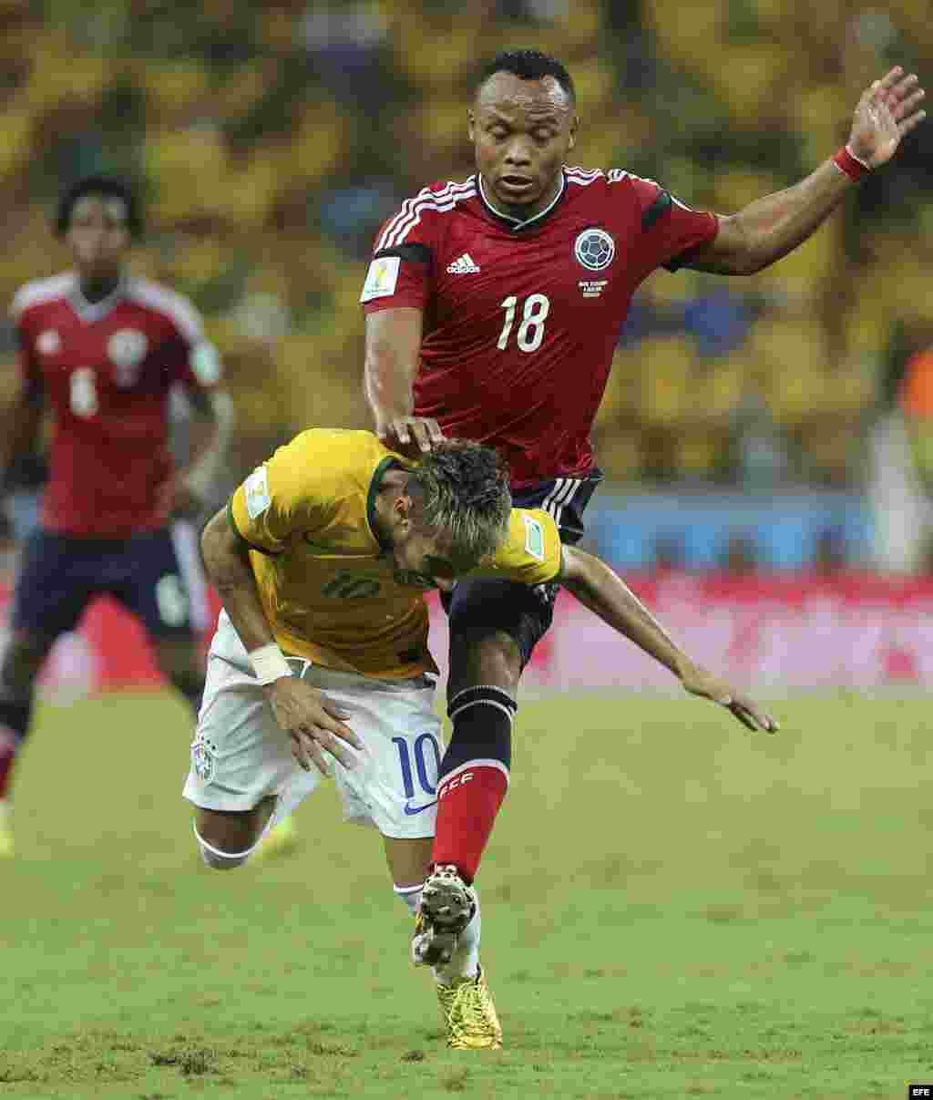 El delantero brasileño Neymar (i) cae ante el defensa colombiano Juan Zúñiga, durante el partido Brasil-Colombia, de cuartos de final del Mundial de Fútbol de Brasil 2014, en el Estadio Castelão de Fortaleza, Brasil.