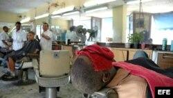Un cliente se somete a un tratamiento de belleza en una barbería en Santiago de Cuba.