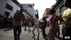 """Personas afines al Gobierno cubano bailan y mantienen rodeada la sede de las Damas de Blanco y les impiden asistir a la iglesia para celebrar el día de la virgen de """"La Merced"""", patrona de los presos."""