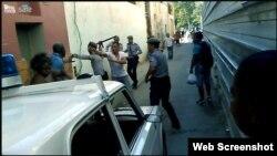 Jorge Anglada Mayeta, amenazado a punta de pistola por un oficial de policía vestido de civil.