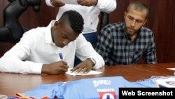 Maykel Reyes firma el contrato con el club mexicano Cruz Azul, mientras Abel Martínez espera su turno.