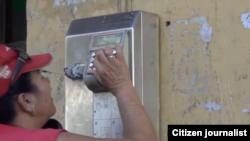 Reporta Cuba. Una mujer intenta comunicarse desde un teléfono público en Centro Habana.