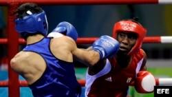 Archivo - El cubano Yordenis Ugas, (rojo) en acción frente al rumano Georgian Popescu durante el combate de boxeo de cuartos de final de los Juegos Olímpicos de Pekín 2008.