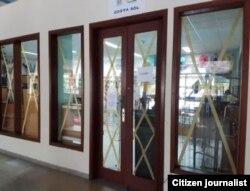 """Tiendas cerradas y vidrios """"asegurados"""" con cinta adhesiva en el Blau Costa Verde de Guardalavaca."""