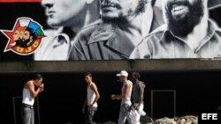 Un grupo de jóvenes camina frente a un cartel alusivo a la Unión de Jóvenes Comunistas (UJC).