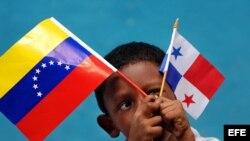 Un niño panameño sostiene la bandera de su país y la de Venezuela.