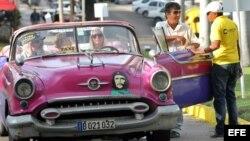 Un grupo de turistas pasea en un auto clásico con una pegatina de Ernesto Guevara. EFE