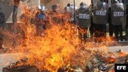 Estudiantes queman muñecos y un ataúd frente a la policía durante una protesta en apoyo a los médicos de Bolivia.