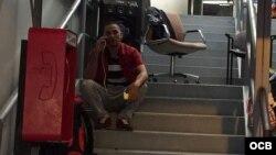 Tras aliviarse de su mochila, un cubano llama a su familia en EE.UU. desde las oficinas de Cubanos en Libertad (C.Matos)