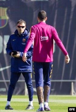 Luis Enrique (i) habla con el centrocampista Sergio Busquets (d) durante la sesión de entrenamiento.
