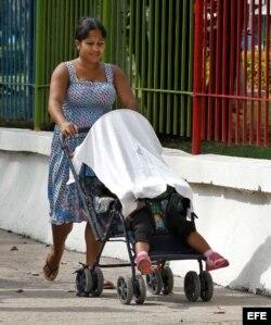 Una mujer camina con un niño, en un coche para bebé en La Habana.