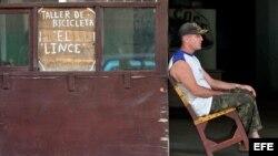 Un hombre permanece sentado en la puerta de un taller de reparación de bicicletas en La Habana