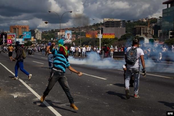 Un grupo de personas se enfrenta a miembros de la Policía Nacional Bolivariana al finalizar la marcha.