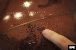 Un científico señala, en un globo de Marte, el cráter Gale en el que ha aterrizado el vehículo explorador Curiosity.