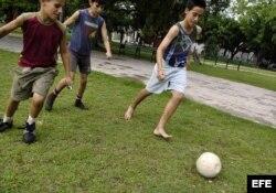 Varios niños cubanos juegan con un balón de fútbol.