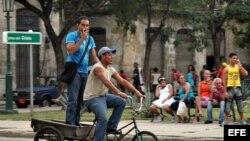 Dos hombres viajan en un triciclo por la zona colonial de La Habana (Cuba).