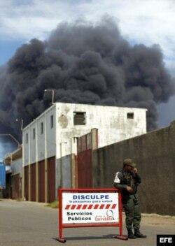 Un miembro de la Guardia Nacional vigila hoy, lunes 27 de agosto de 2012, los alrededores de la refinería de Amuay, que continúa ardiendo, en el Estado Falcón, Venezuela.