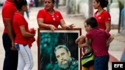 Un grupo de personas llevan un cuadro con la imagen de Fidel Catro mientras esperan la llegada de la caravana que traslada sus cenizas. (Archivo)