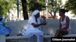 Reporta Cuba. En el parque de la Fraternidad, una cartomántica (i) le lee las cartas a una joven Foto: Bárbara Fernández.
